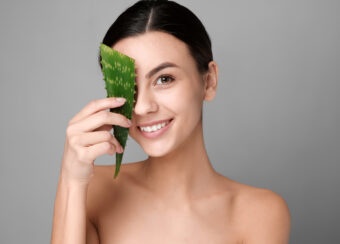 Portrait of beautiful woman with aloe vera on grey background